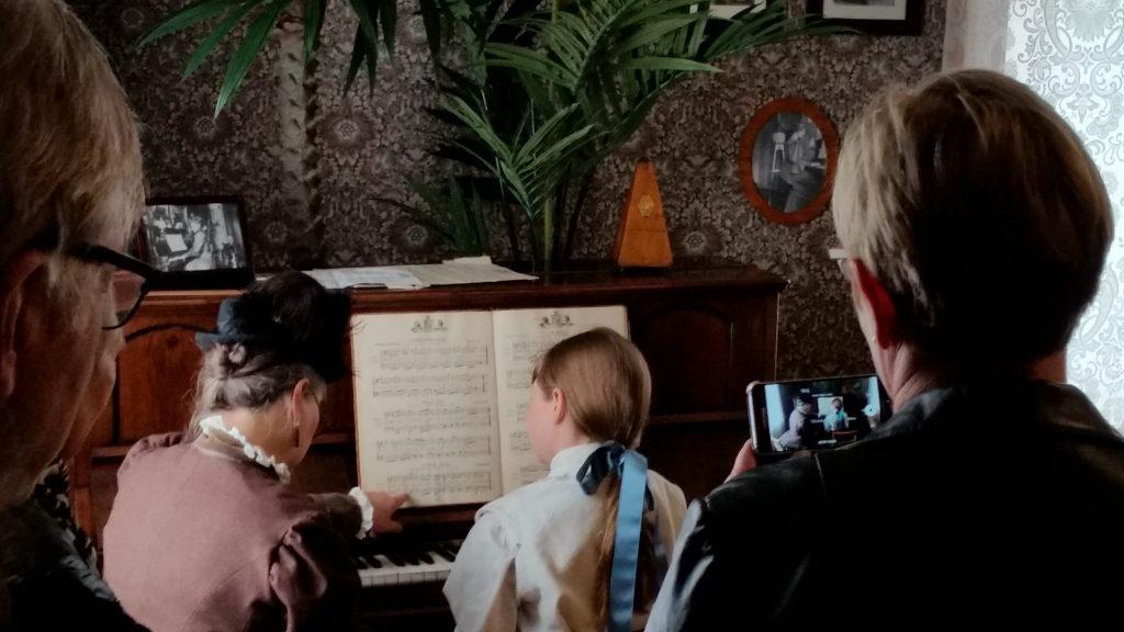 Pianoundervisning som i 1880 i stue på Ringve musikkmuseum. Myndig pianolærer for ung pike.