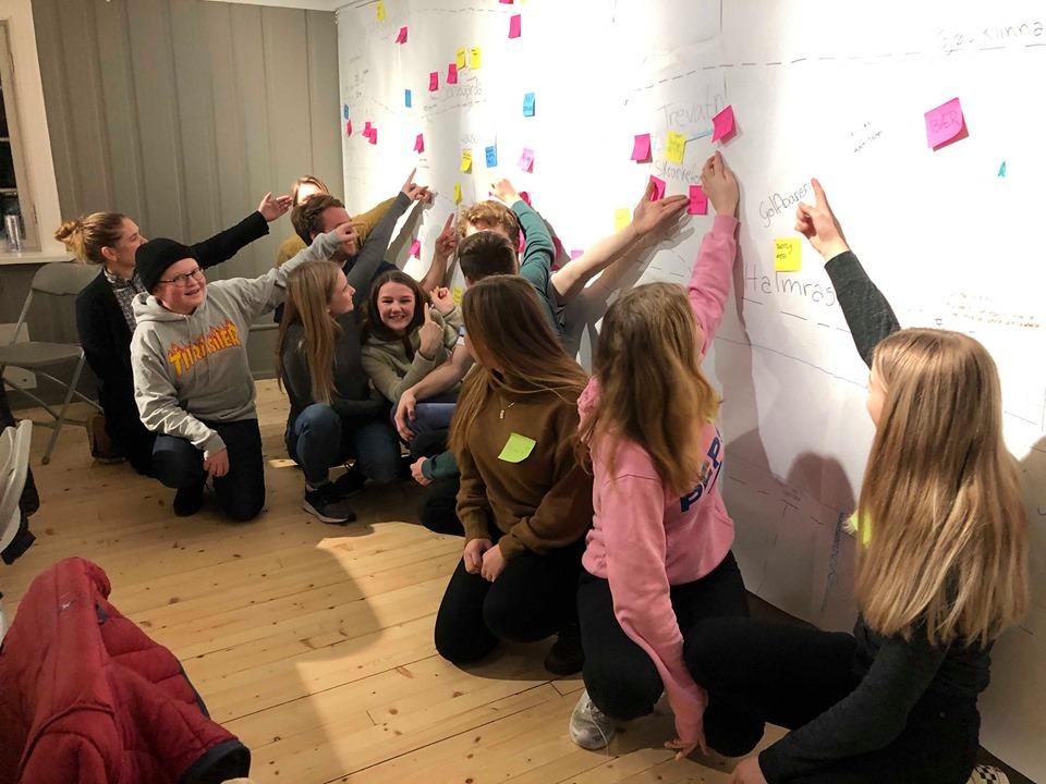 Barn peker på sitt favorittsted på en tavle med skrift og Pist It-lapper.