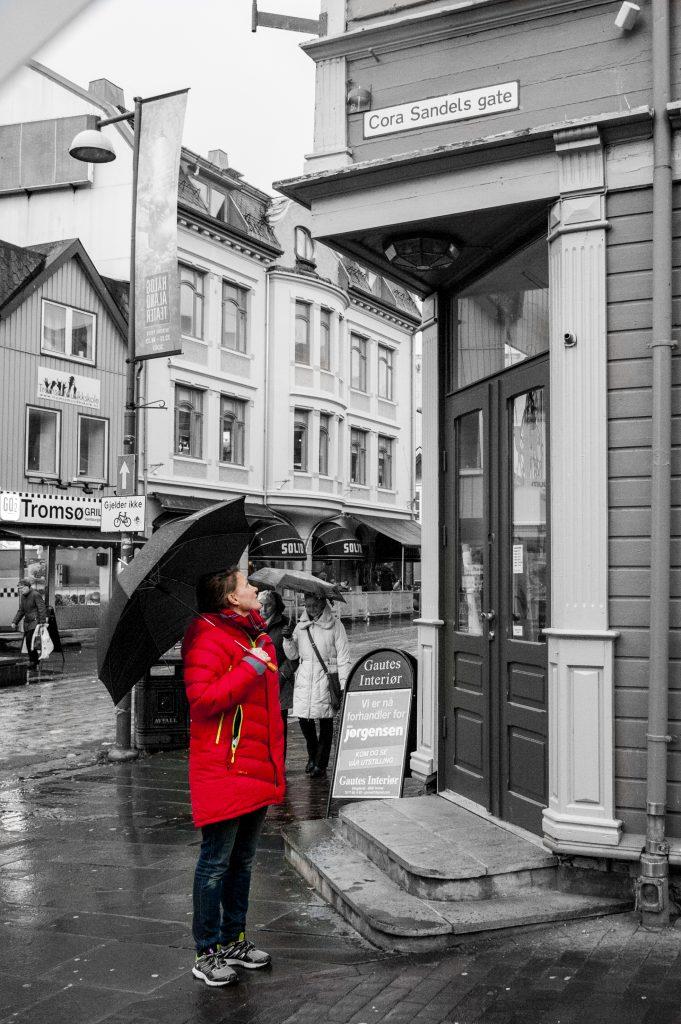 I 2006 fikk Tromsø en Cora Sandels gate. Kvinne i rød jakke står foran Cora Sandels gate, titter opp på skiltet og holder i en paraply.