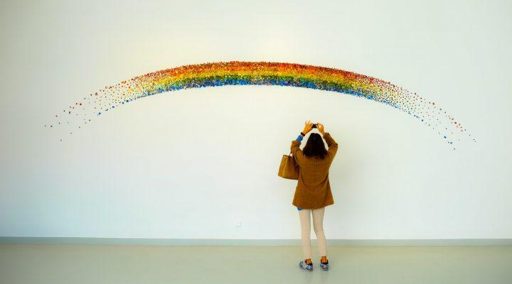 Jente tar bilde av regnbue malt på veggen.
