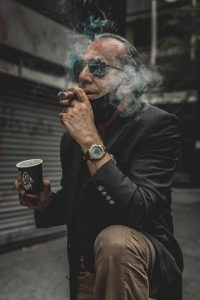 Mann med solbriller, dressjakke og beige bukser, drikker kaffe og røyker sigarett. Munnbindet er dratt ned på haken.