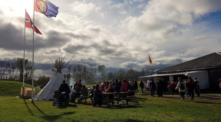 samling foran Várjjat Sámi museat, sola skinner og både det norske og det samiske flagget vaier i vinden.