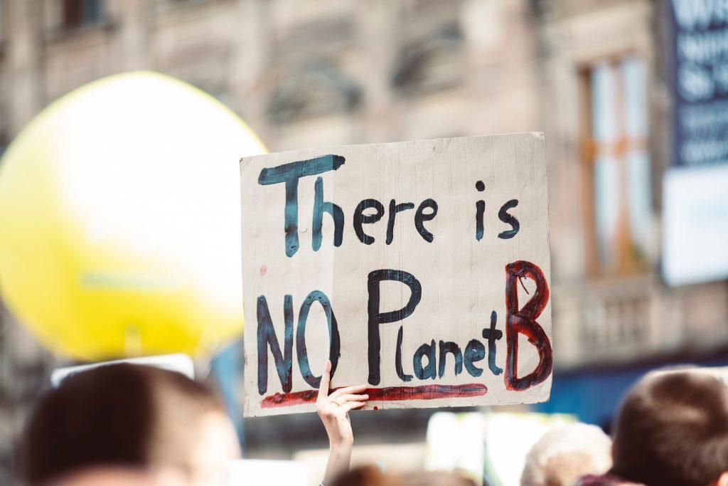 """Plakat holdes opp under demonstrasjon. """"There is no planet B"""" står det på plakaten."""