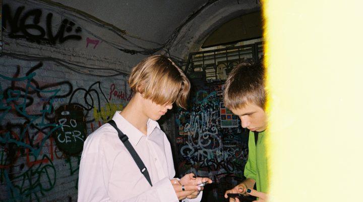 Personer holder på med spill-konsoller, omkranset av vegger med grafitti.