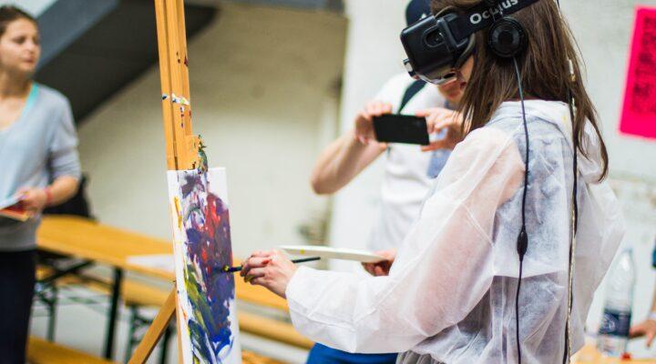 Jente maler med VR-briller på hodet.